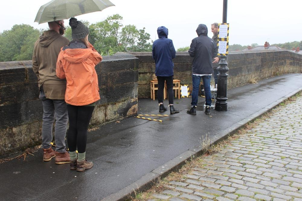 People queuing by the River Ribble to stamp their words into silver coins.