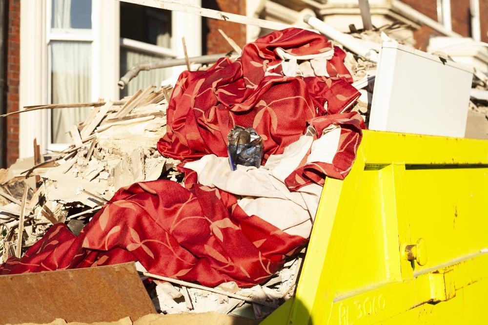 Glass of mussels in a skip filled with fabric and wood
