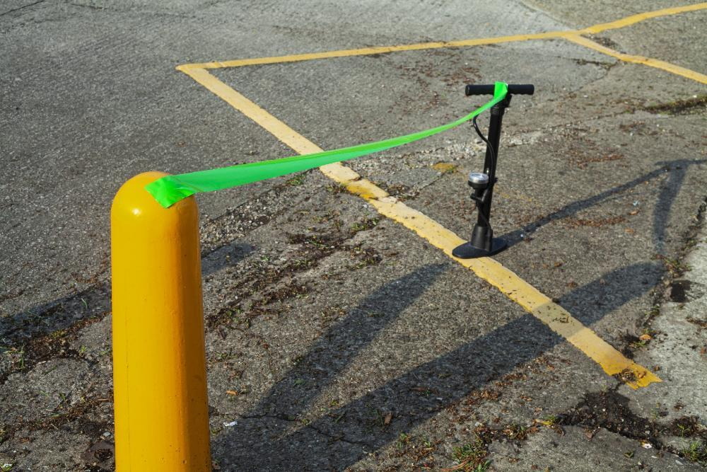 Bicycle pump and yellow bollard joined by green tape