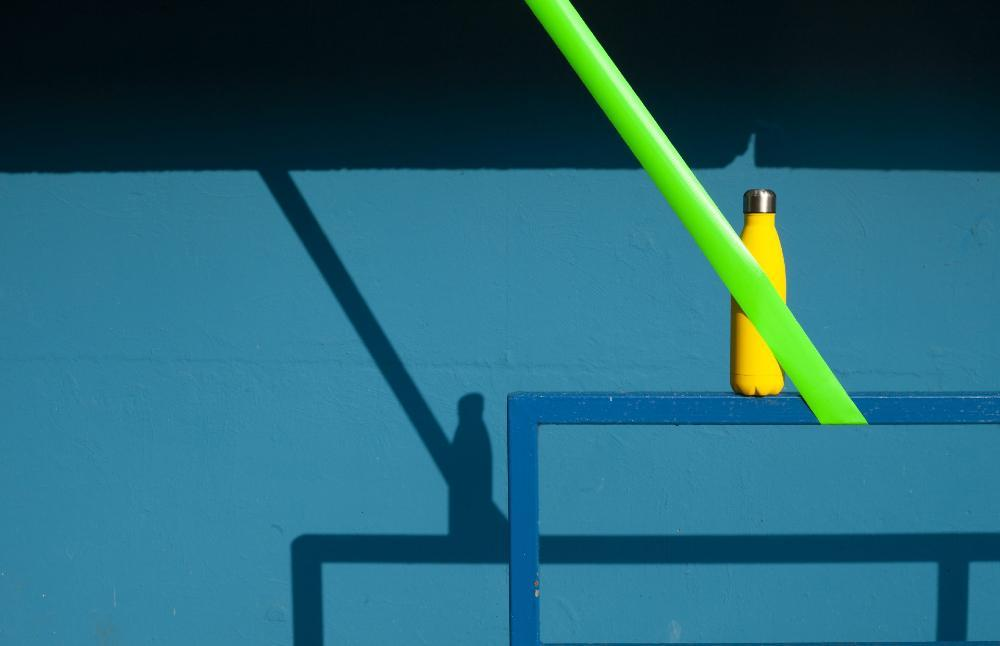 Yellow drinking bottle with green tape in front of it, against a blue background