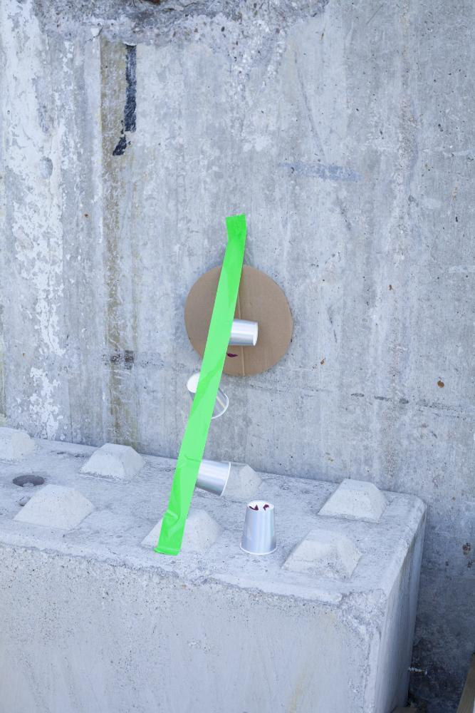 Abstract street creation using a cardboard circle, silver cups and green tape