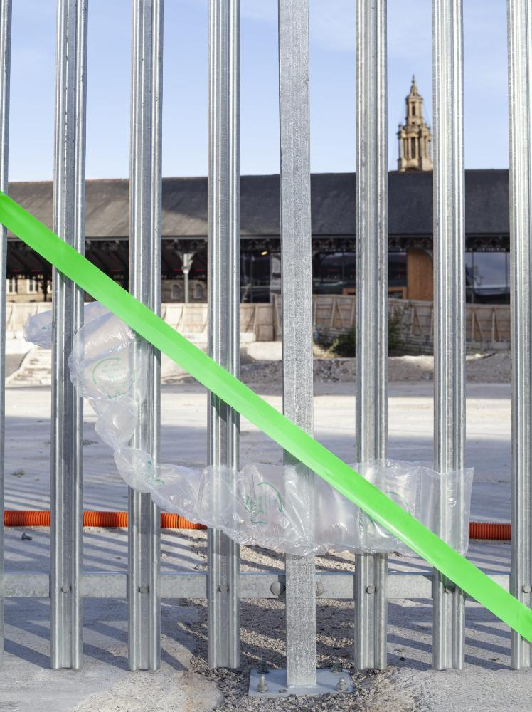 View through metal fence with green tape and plastic over it, looking into building site by Preston Markets