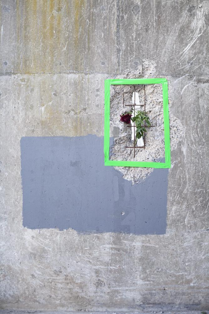 Abstract street creation with red flower inside a green tape box against cement