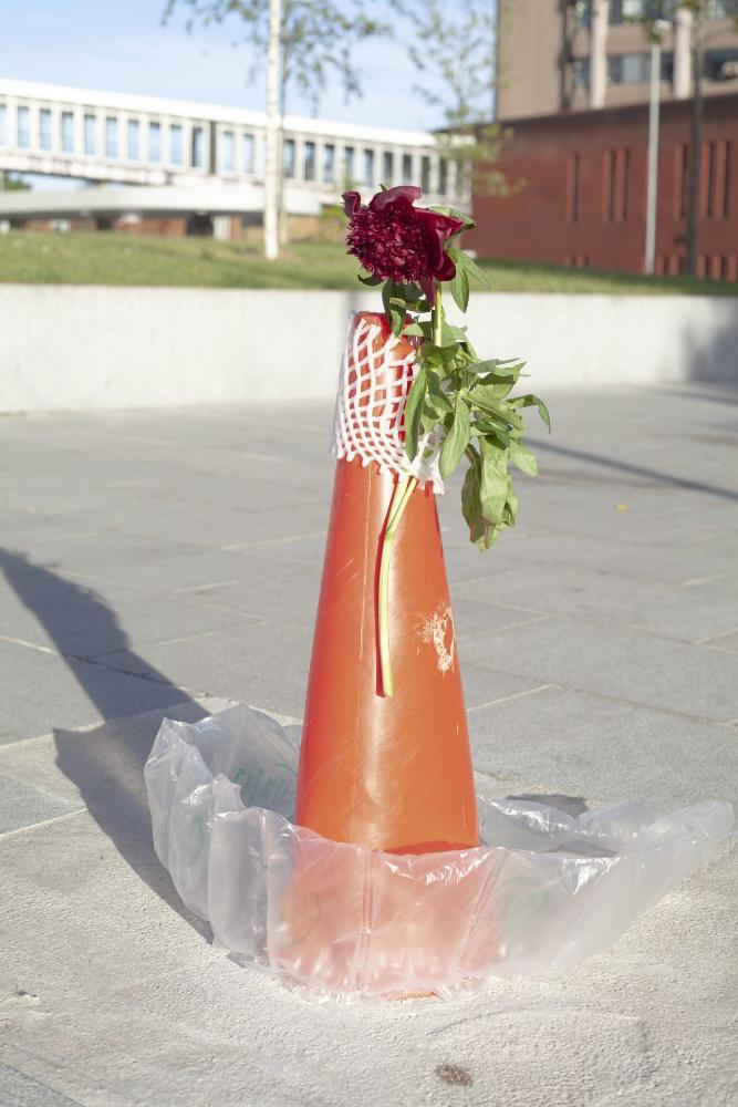 Abstract street creation using an old traffic cone, waste and a flower