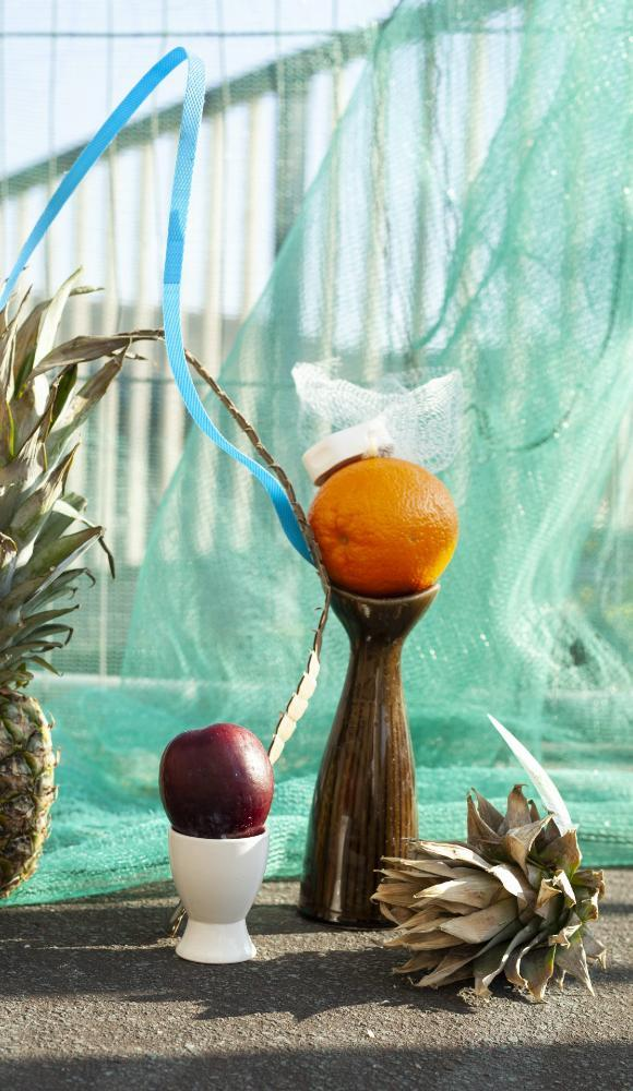 Abstract street creation featuring an apple in an egg cup, an orange in a vase and a pineapple, arranged on a wall