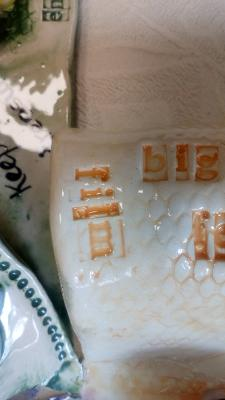 Close up of a ceramic windmill sail painted orange and glazed, with words stamped in.