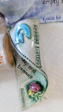 """Ceramic windmill sail painted green and glazed, with Preston Guild logo on and words saying """"annual festival""""."""