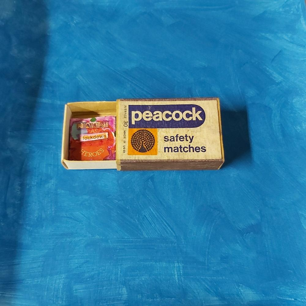 """Image 9: Peacock safety matches matchbox, open with small abstract piece of art inside, also including the word """"lockdown""""."""