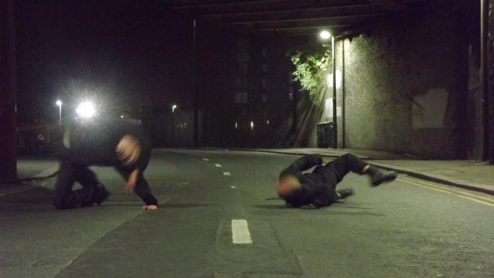 Two men moving across a road at night, blurred with movement.