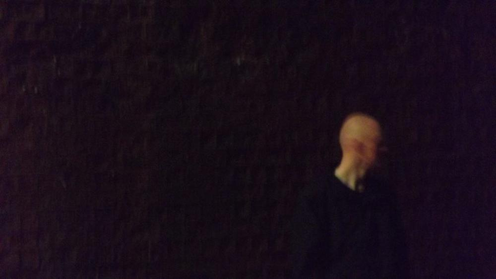 Man standing against a wall at night, his face blurred with movement.